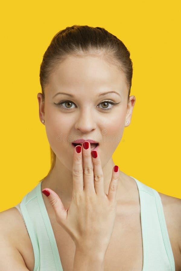 Stående av en härlig häpen ung kvinna med handen över mun över gul bakgrund