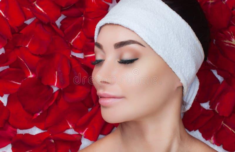 Stående av en härlig kvinna i en brunnsortsalong framme av en skönhetbehandling mot bakgrunden av röda roskronblad arkivfoto