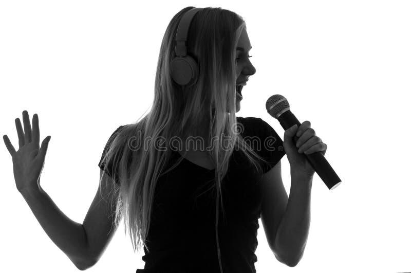 Stående av en härlig kvinna i hörlurar och med en mikrofon arkivfoto