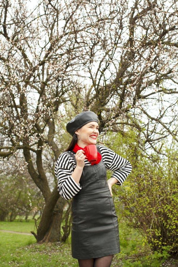 Stående av en härlig kvinna i sripped tröja med koppen i trädgård för blomningäppleträd i vårtid royaltyfria foton