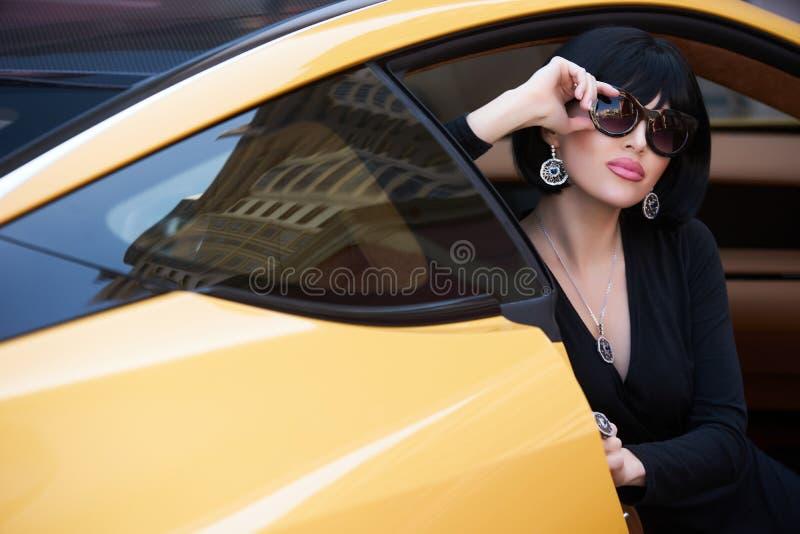 Stående av en härlig kvinna med den gula sportbilen royaltyfria bilder