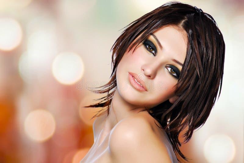 Stående av en härlig kvinna med den idérika frisyren. arkivfoto