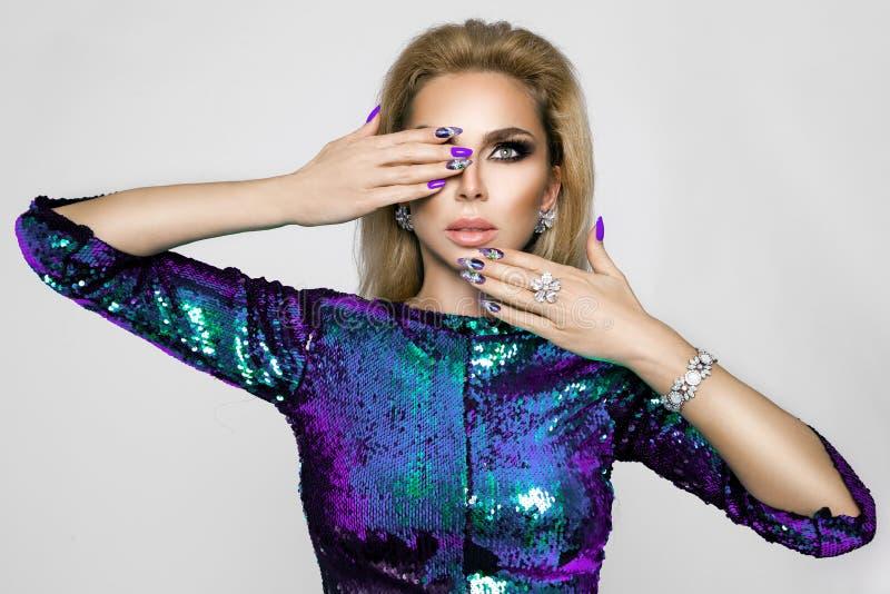 Stående av en härlig kvinna med elegant makeup- och innegrejmanikyr arkivbild