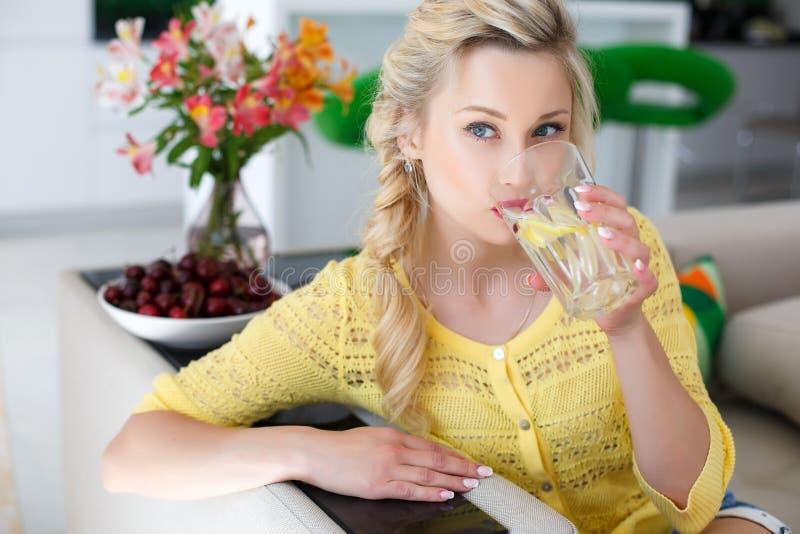 Stående av en härlig kvinna med ett exponeringsglas av vatten i köket fotografering för bildbyråer