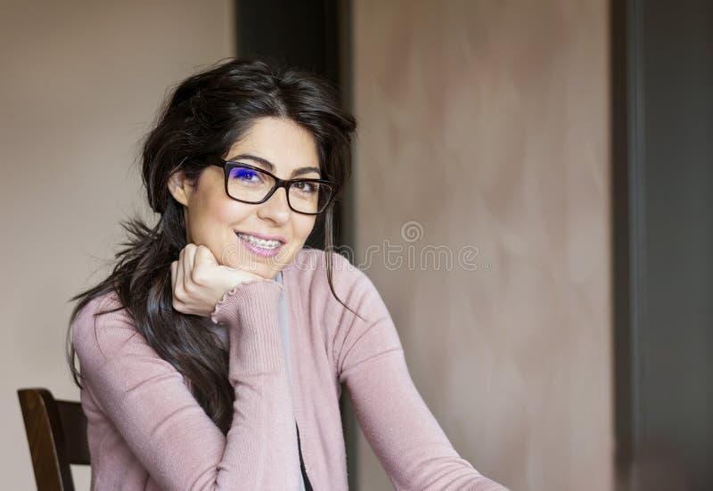 Stående av en härlig kvinna med hänglsen på tänder orthodontic behandling Isolerat över vit bakgrund arkivfoton