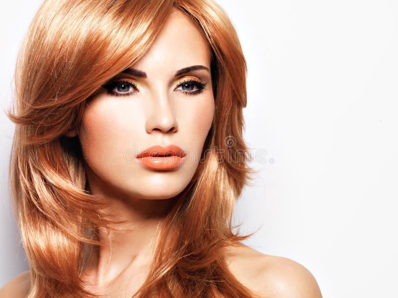 Stående av en härlig kvinna med långt rakt rött hår royaltyfri foto
