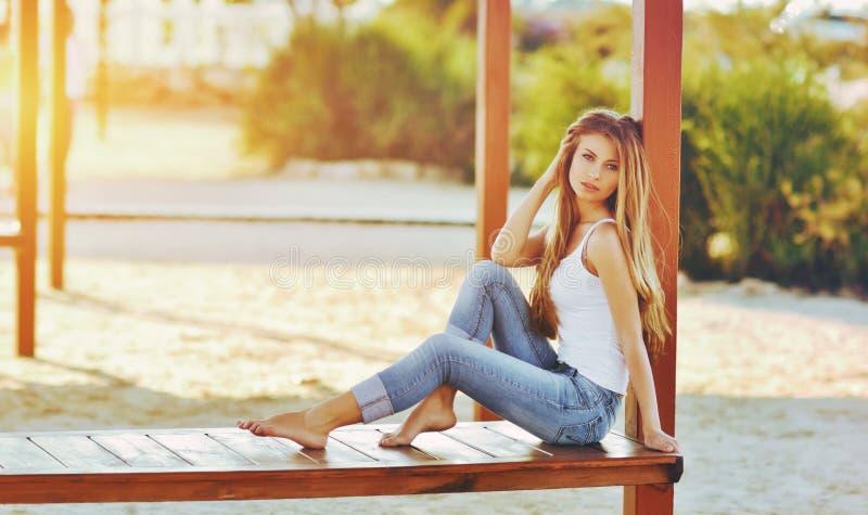 Stående av en härlig kvinna med storartat hår i en vit överkant och en stilfull jeans fotografering för bildbyråer
