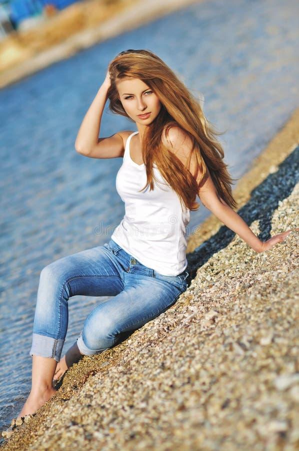 Stående av en härlig kvinna med storartat hår i en vit överkant och en stilfull jeans arkivfoton