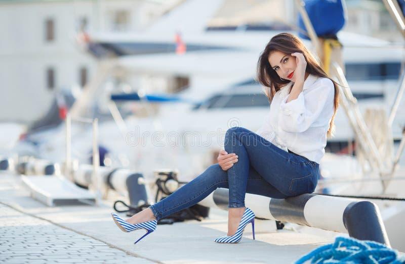 Stående av en härlig kvinna på bakgrunden av havet och yachterna royaltyfri foto