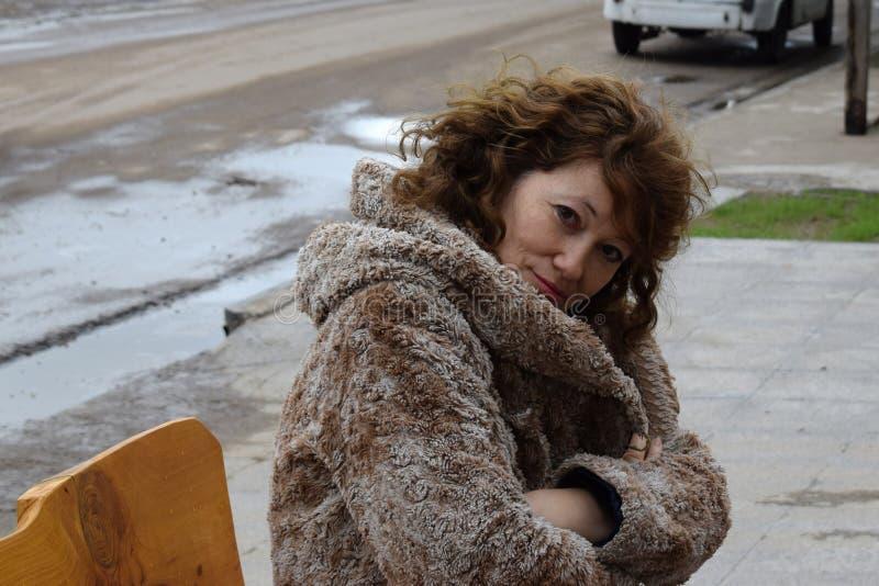 Stående av en härlig kvinna på det fria för en bänk i höst royaltyfri foto