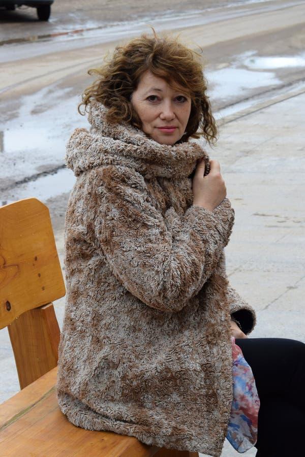 Stående av en härlig kvinna på det fria för en bänk i höst royaltyfri bild