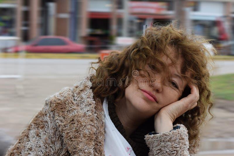 Stående av en härlig kvinna på det fria för en bänk i höst fotografering för bildbyråer