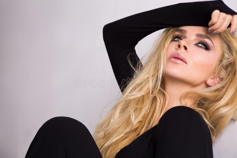 Stående av en härlig kvinna på en vit bakgrund och ett långt lockigt blont hår och en sinnlig mun med långa snärtar som bär en bl fotografering för bildbyråer