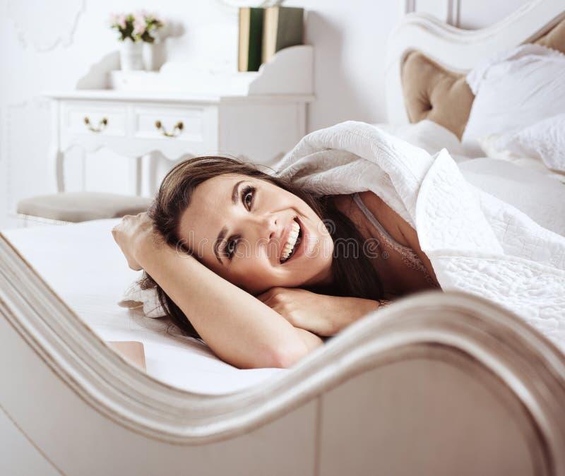 Stående av en härlig kvinna som kopplar av i säng fotografering för bildbyråer