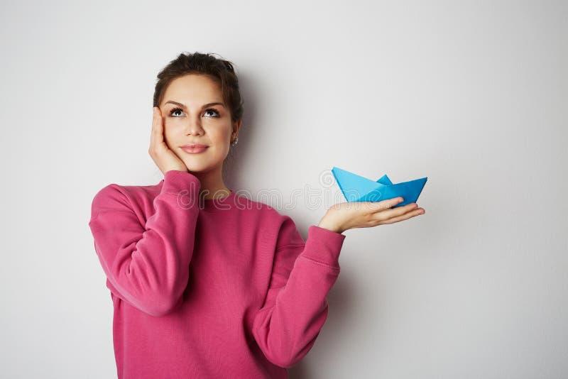 Stående av en härlig kvinna som rymmer ett skepp för blått papper på tom grå bakgrund Sinnesrörelser folk, skönhet, mode och arkivbild
