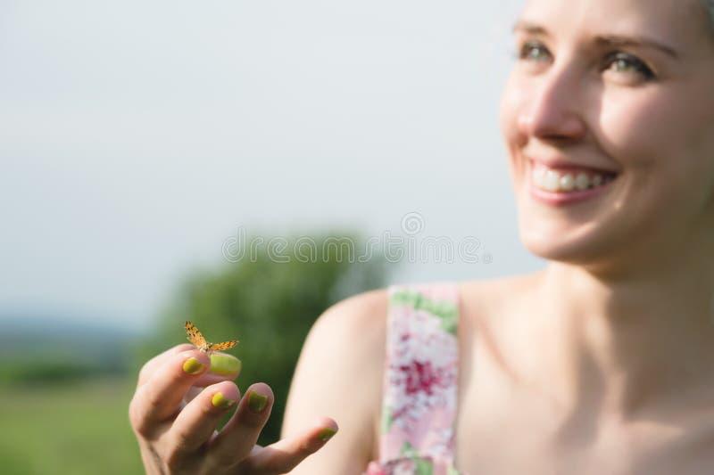 Stående av en härlig kvinna som rymmer en fjäril på hennes hand i trädgården skönhet isolerad ståendewhite Enhet med naturen ekol arkivbild