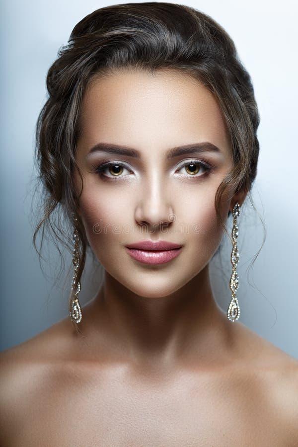 Stående av en härlig kvinnacloseup Perfekt ren hud, härligt hår, yrkesmässig makeup bakgrundsdiamanter isolerade stilfull white f royaltyfri foto