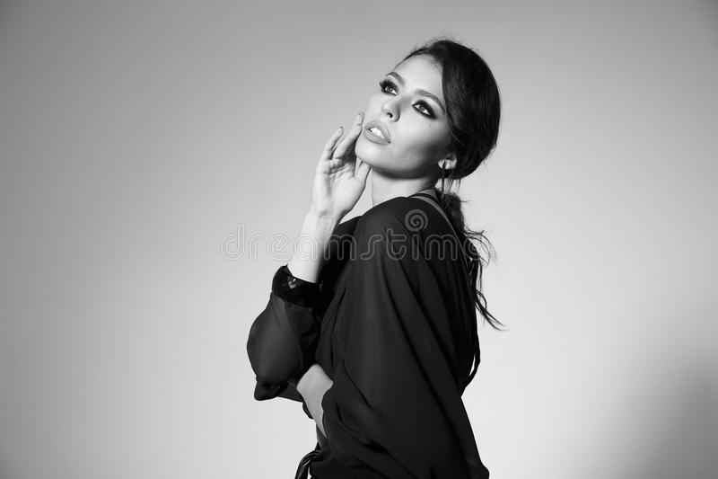 Stående av en härlig kvinnlig modell i en svart klänning arkivbilder