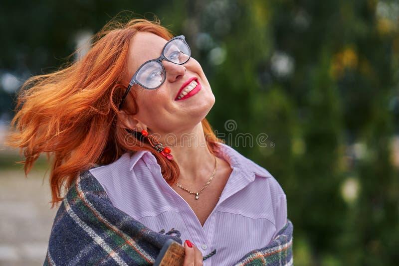Stående av en härlig le medelålders kvinna med bärande exponeringsglas för rött hår på en molnig dag royaltyfri foto