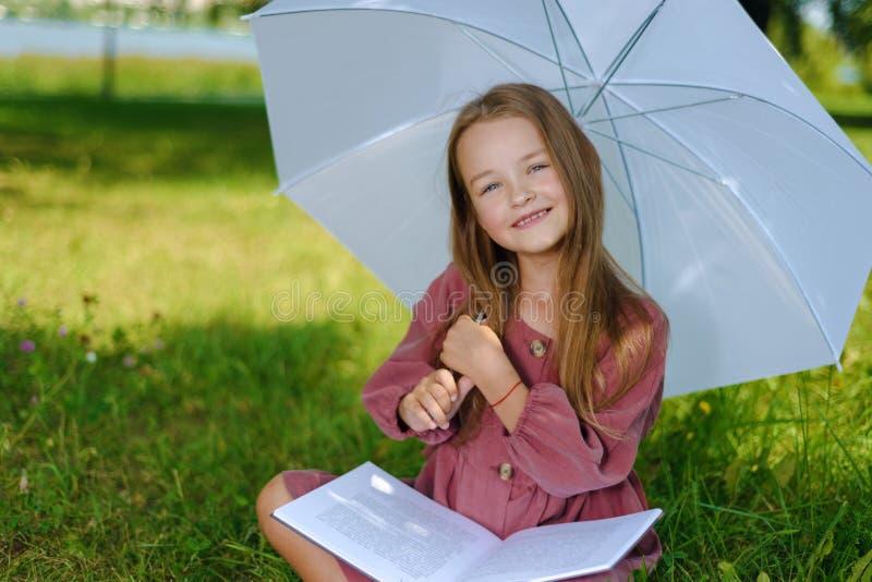 Stående av en härlig liten flicka i den burgundy kappan barnet ler och läser boken parkerar in fotografering för bildbyråer