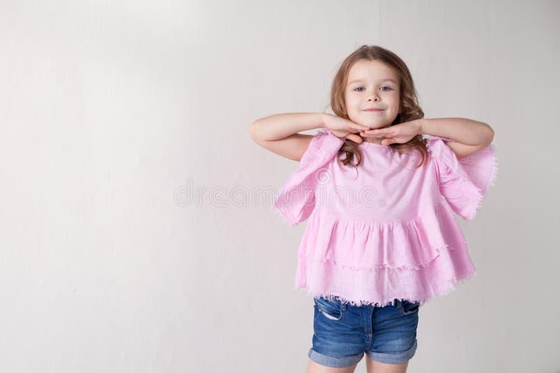 Stående av en härlig liten flicka i en rosa klänning fem år royaltyfri fotografi