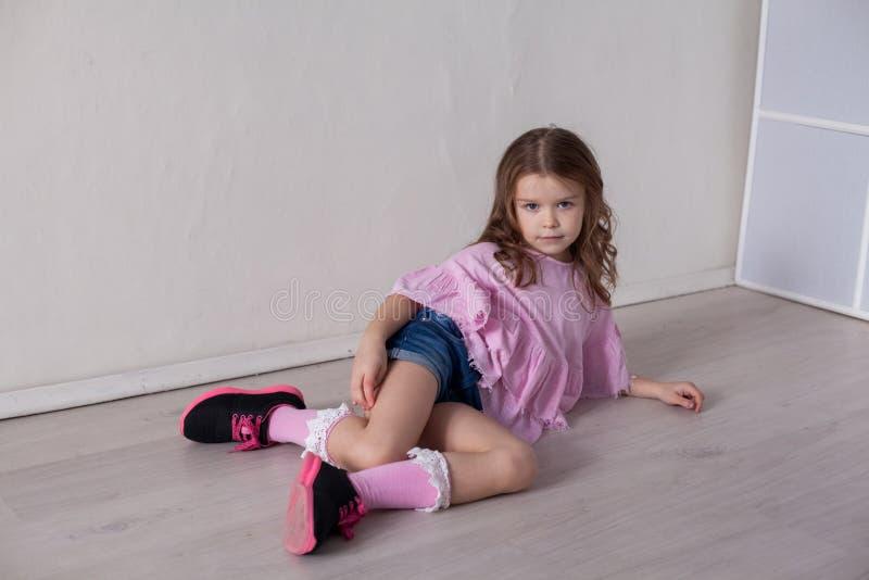 Stående av en härlig liten flicka i en rosa klänning fem år arkivbilder