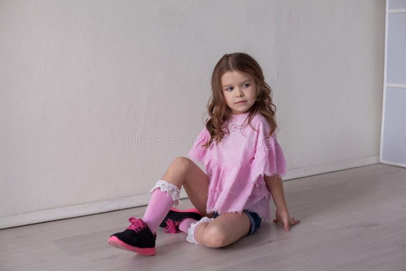 Stående av en härlig liten flicka i en rosa klänning fem år arkivbild