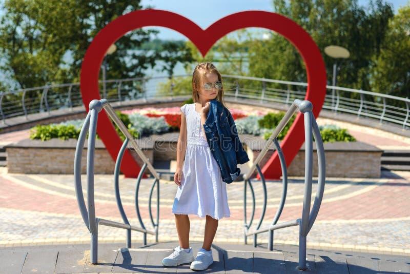 Stående av en härlig liten flicka i en vit klänning i solglasögon arkivfoton