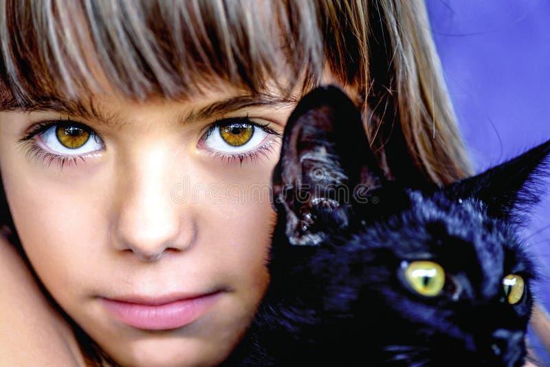Stående av en härlig liten flicka som rymmer en svart katt royaltyfri fotografi