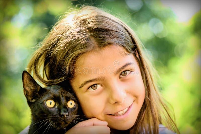 Stående av en härlig liten flicka som rymmer en svart katt royaltyfri bild