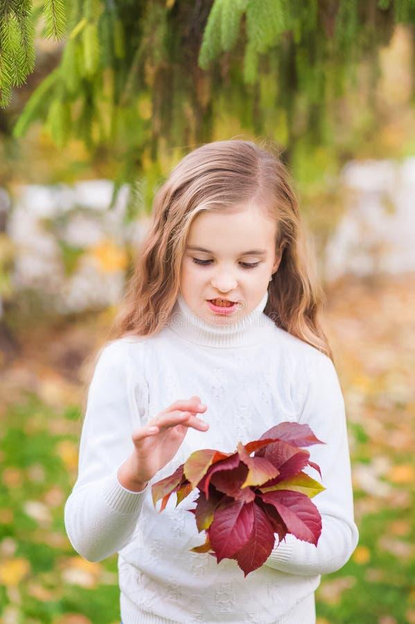 Stående av en härlig liten flickanärbild i en vit tröja på en bakgrund av grön textural naturlig bakgrund Flickan lurar royaltyfria foton
