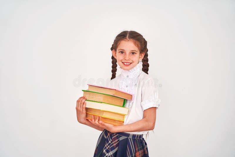Stående av en härlig liten flickastudent med en ryggsäck och en bunt av böcker i hans händer som ler på en vit bakgrund arkivfoton