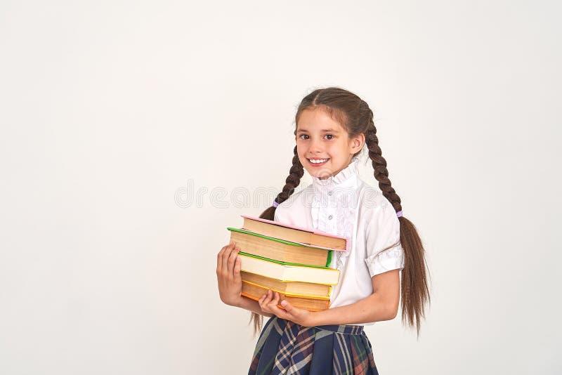 Stående av en härlig liten flickastudent med en ryggsäck och en bunt av böcker i hans händer som ler på en vit bakgrund royaltyfri foto