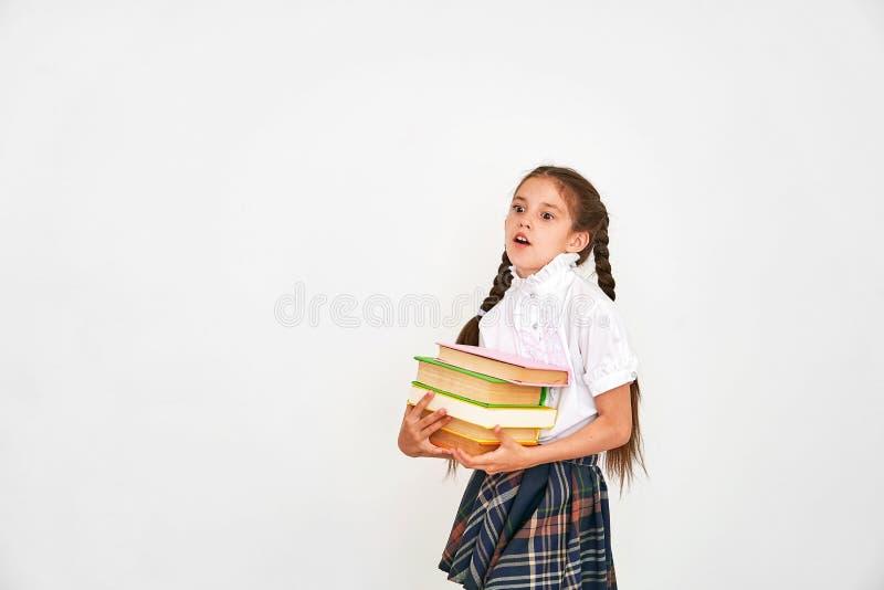 Stående av en härlig liten flickastudent med en ryggsäck och en bunt av böcker i hans händer som ler på en vit bakgrund royaltyfria bilder
