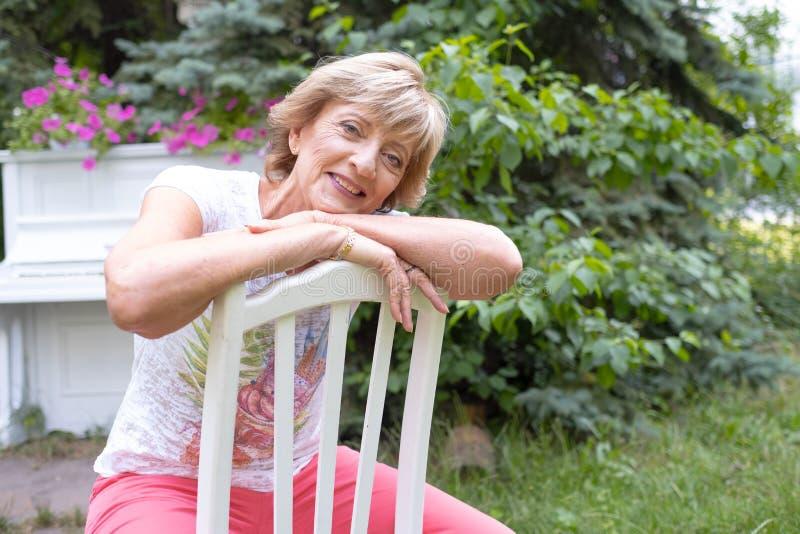 Stående av en härlig, lycklig och smart farmor som sitter på den utomhus- stolen royaltyfria foton