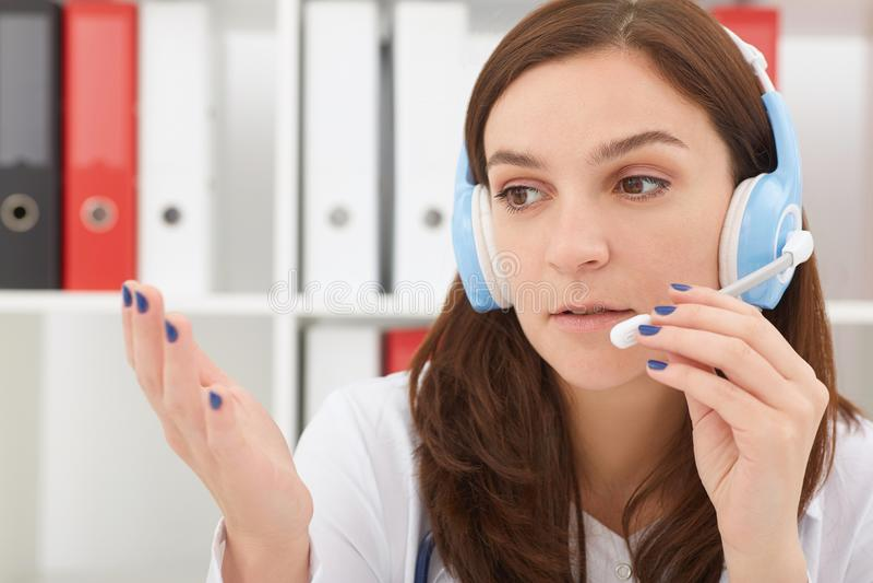 Stående av en härlig medicinsk sekreterare med telefonluren på sjukhuset MEDICINSKT begrepp royaltyfri bild