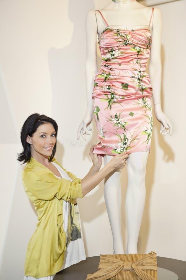 Stående av en härlig mitt- vuxen kvinna som justerar klänningen på skyltdocka i modeboutique royaltyfri bild