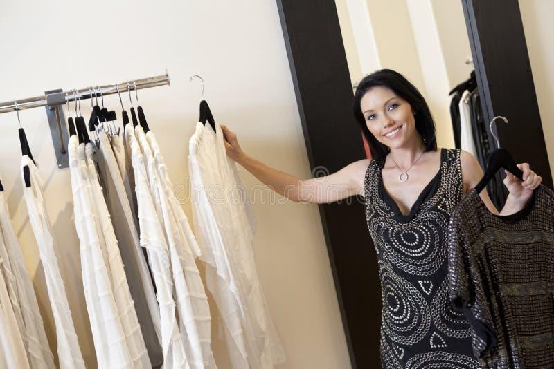 Stående av en härlig mitt- vuxen kvinna som väljer klänningen från kuggen i modeboutique arkivfoto