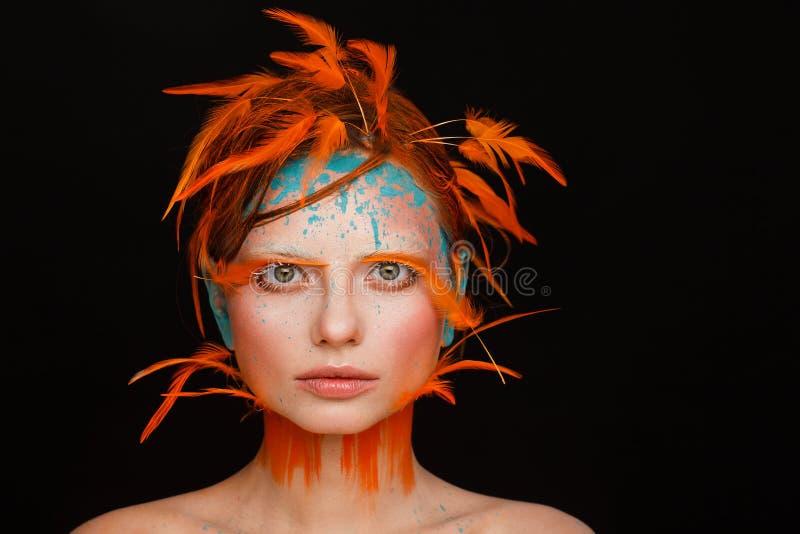 Stående av en härlig modell med idérikt smink och frisyren genom att använda orange fjädrar royaltyfri foto