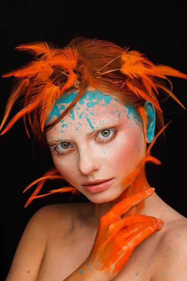 Stående av en härlig modell med idérikt smink och frisyren genom att använda orange fjädrar fotografering för bildbyråer