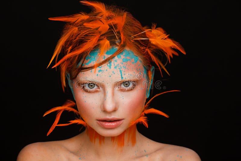 Stående av en härlig modell med idérikt smink och frisyren genom att använda orange fjädrar arkivbild