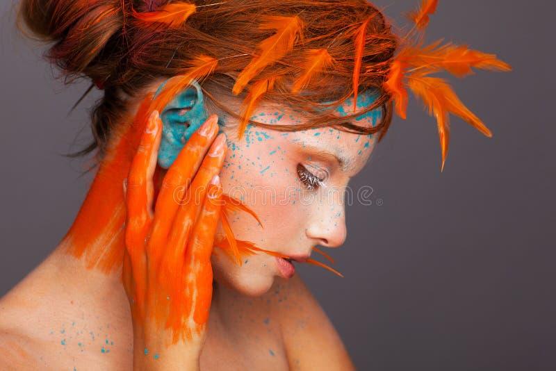 Stående av en härlig modell med idérikt smink och frisyren genom att använda orange fjädrar royaltyfri fotografi
