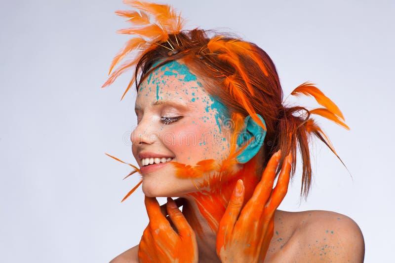Stående av en härlig modell med idérikt smink och frisyren genom att använda orange fjädrar arkivfoton