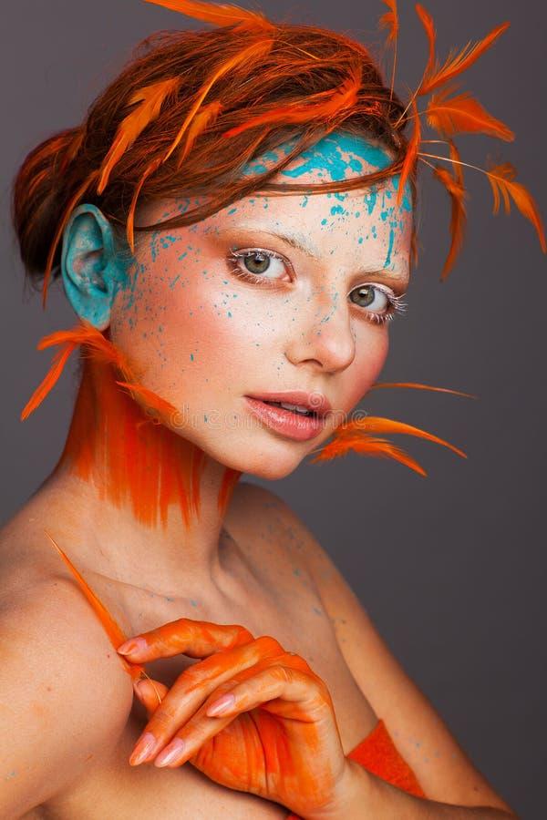 Stående av en härlig modell med idérikt smink och frisyren genom att använda orange fjädrar royaltyfri bild