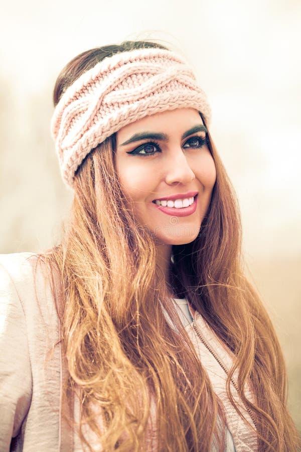 Stående av en härlig och le kvinna med den rosa huvudbindeln och långt hår arkivfoton
