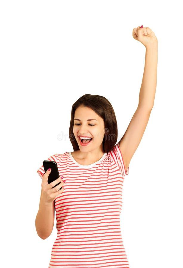 Stående av en härlig och lycklig ung kvinna som ser in i telefonen och firar något emotionell flicka som isoleras på vit b royaltyfri foto