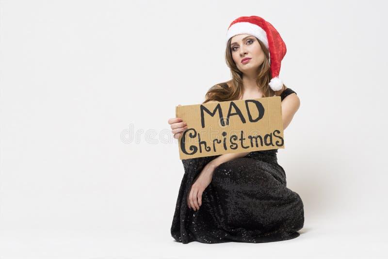 St?ende av en h?rlig olycklig brunettkvinna i julhatt i en elegant svart festlig kl?nning som tokig jul rymmer f?r ett tecken ? arkivbild