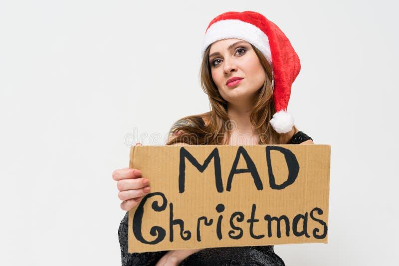 St?ende av en h?rlig olycklig brunettkvinna i julhatten som tokig jul rymmer f?r ett tecken ?p? en vit bakgrund F?f?nga hol arkivbild