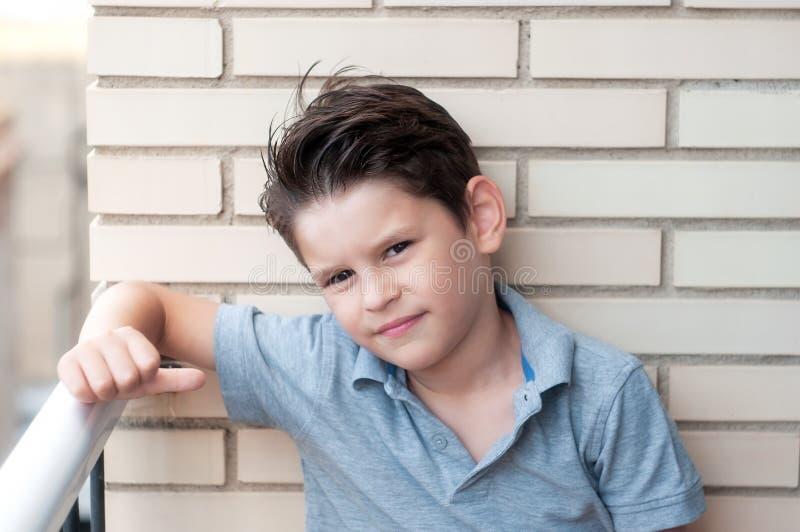 Stående av en härlig pojke i en tegelstenvägg Säkert barn, mummel arkivbilder
