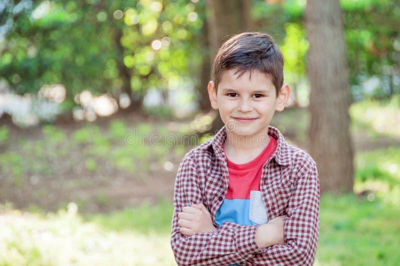 Stående av en härlig pojke i parkera som står med armcros royaltyfria foton